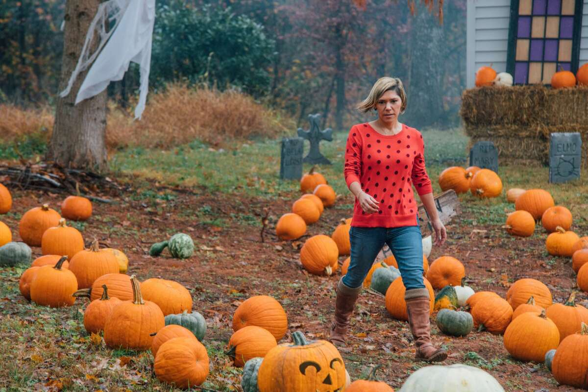 """Chrissy Scarpati of Monroe searches the pumpkin patch for pumpkin to carve, as seen on Food Network's """"Outrageous Pumpkins,"""" Season 2."""