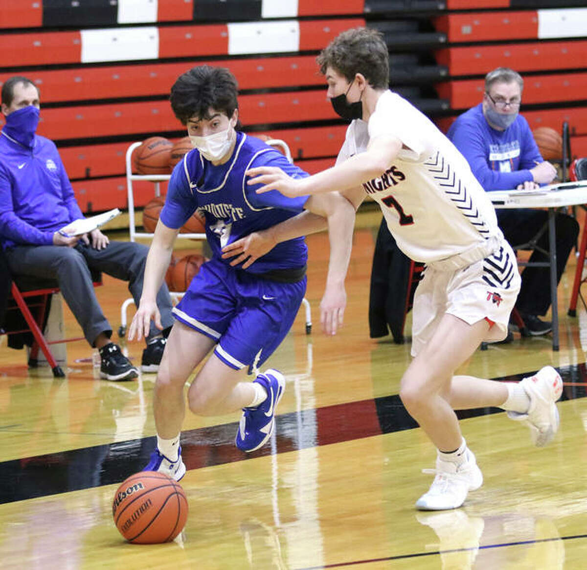 Marquette Catholic's Owen Williams (left) drives past Triad's Jake Stewart during a game last season in Troy. Williams is a senior and will lead an Explorers team in its first season as a member of the new Gateway Metro Conference in the 2021-22 season.