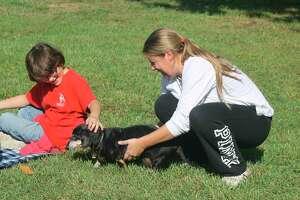 Amnesty Freedom Farm co-owner Megan Scott introduces a Trinity Lutheran School student to Winston the dachshund on Friday. (Kyle Kotecki/News Advocate)