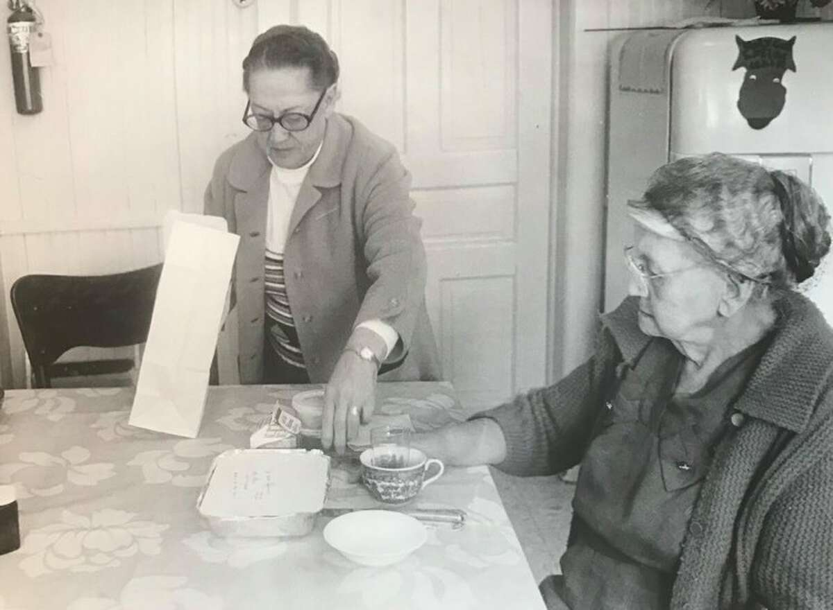 Mrs. Paul Holzinga, volunteer, serves a Mobile Meal to Emma Reed at her home. Holzinga's husband is retired and works regularly as a volunteer driver. March 1975