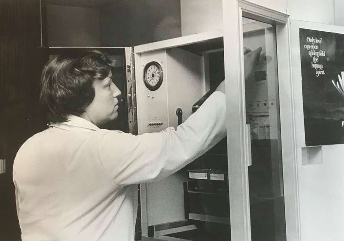 Pauline Fischer, left, selects a video film for the new patient education closed circuit television, which provides information for patients in their rooms. The equipment was purchased with money raised from the Gift Shop Guild. December 1979
