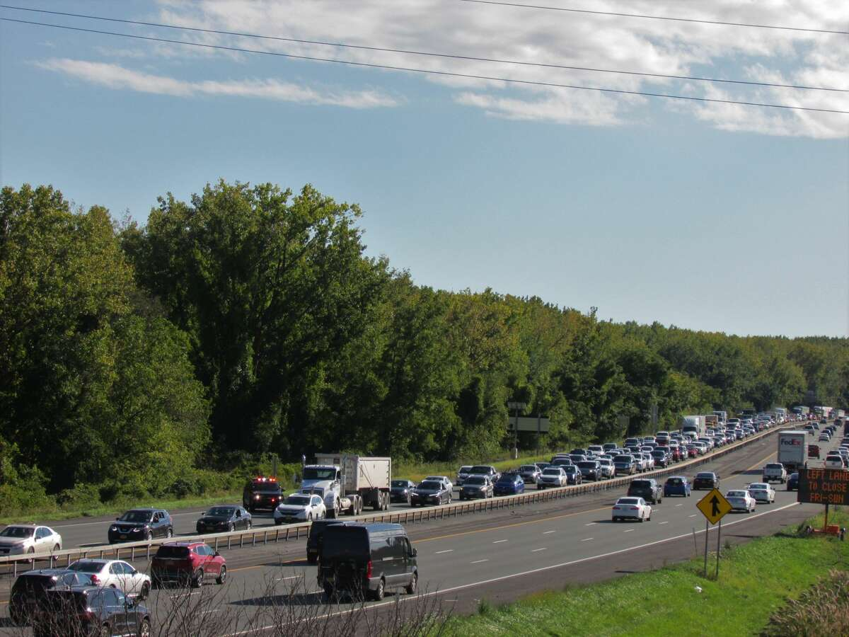 Cars on the northbound side of Interstate 787 slowly make their way past police officers and detectives investigating a shooting in Menands that sent at least one person to the hospital.