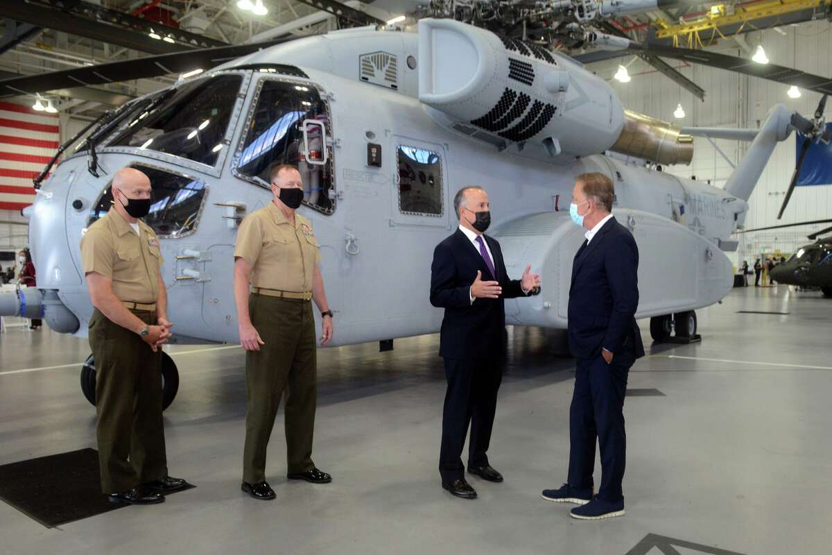 Sikorsky Aircraft President Paul Lemmo, third from left, speaks with Gov. Ned Lamont next to the first Connecticut built Sikorsky CH-54K King Stallion helicopter in a hangar at Sikorsky headquarters in Stratford, Conn. Sept. 24, 2021. The new generation of the CH-53's are being built in Stratford for the U.S. Marines Corps.