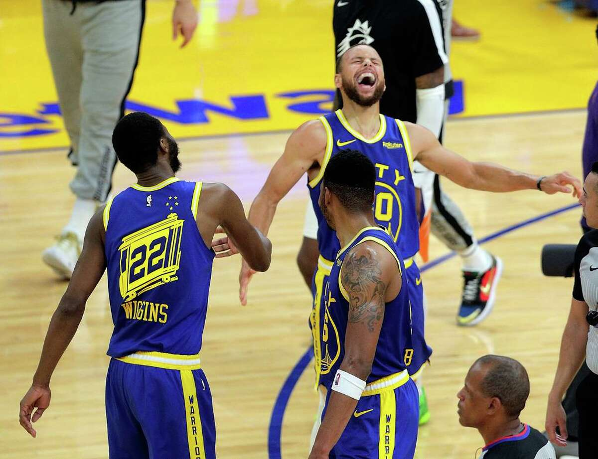 Stephen Curry (30) and Andrew Wiggins (22) celebrate in the second half as the Golden State Warriors defeated the Phoenix Suns 122-116 at Chase Center in May.