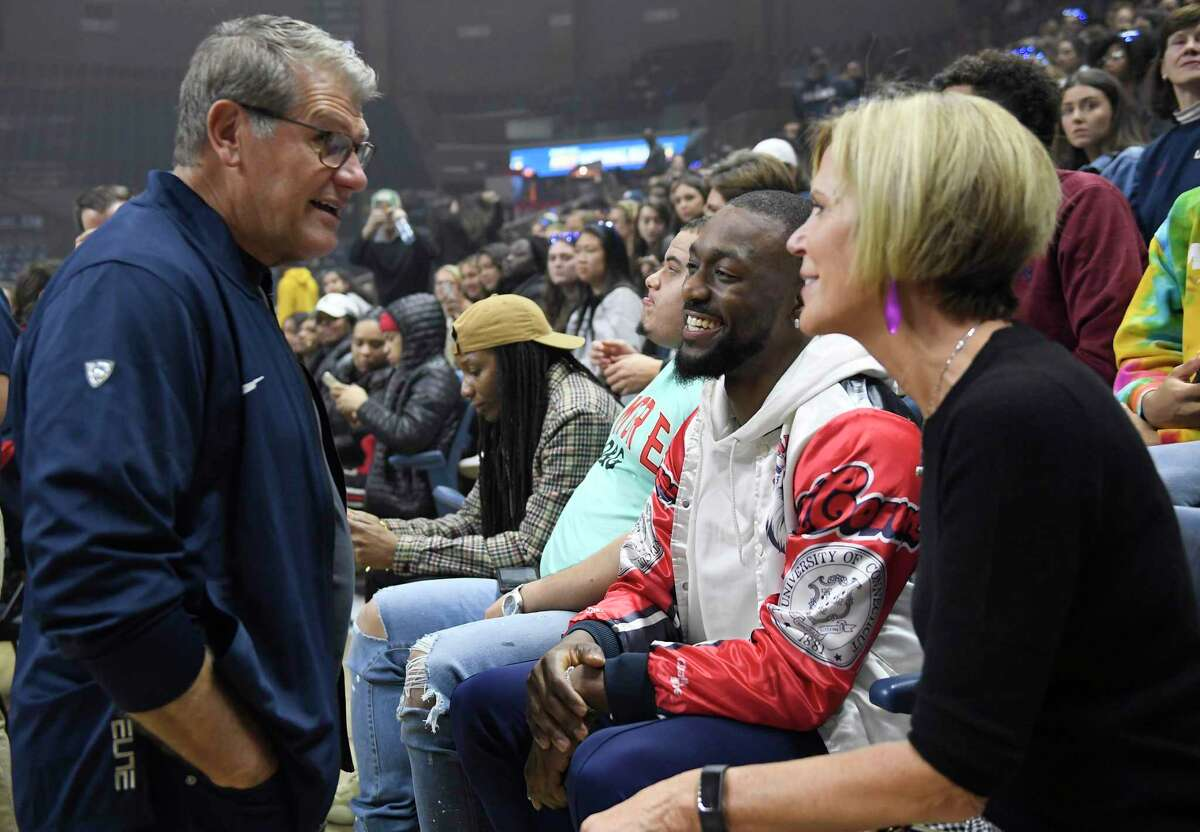 Then-Boston Celtics' and former UConn player Kemba Walker, center right, talks with women's head coach Geno Auriemma, left, and associate coach Chris Dailey during UConn's men's and women's basketball teams' annual First Night celebration in Storrs, Conn. on Oct. 18, 2019. UConn's incoming freshmen will experience First Night, unlike last year's class, in front of students only.