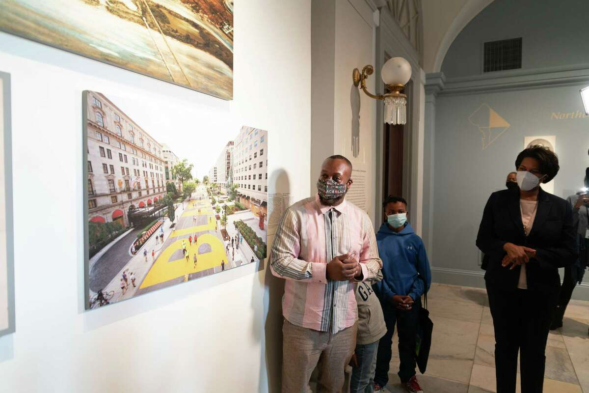 Photographer Khalid Naji-Allah with his two sons and Mayor Muriel E. Bowser in front of his photo of Black Lives Matter Plaza displayed at the National Portrait Gallery.