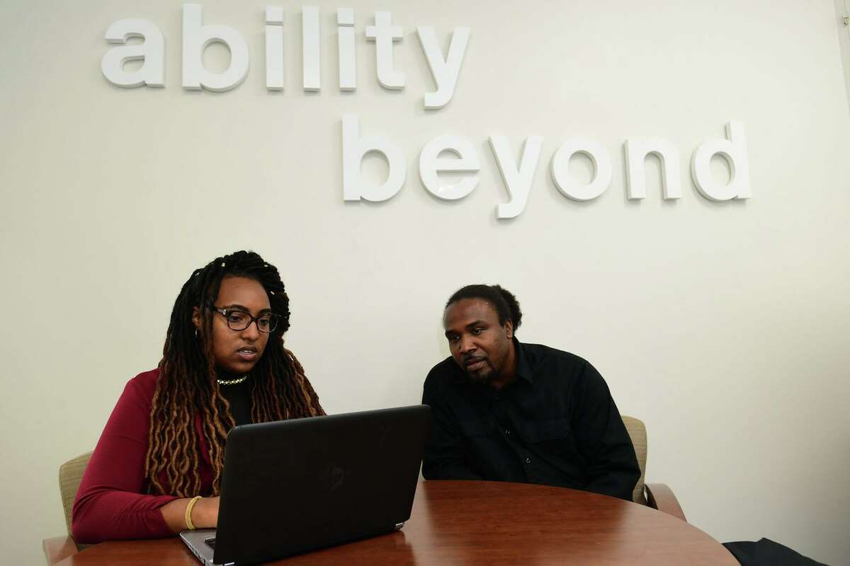 Employment Specialist Chenelle helps client Earl Melton at The Bethel-based disabilities services giant, Ability Beyond facility in Norwalk, Conn. October is national disabilities awareness month.