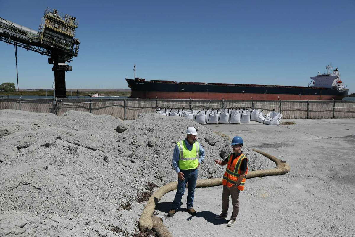 Brent Constantz (left), chief executive officer Blue Planet, and Chris Larsen, co-founder of the Larsen and Lam Climate Initiative, stand next to a pilel of broken down concrete before it is processed as Constantz gives Larsen a tour of SF Bay Aggregates in Pittsburg, a Blue Planet subsidiary.