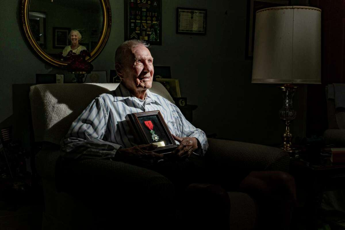World War II veteran Vern Ollar, who is 100 years old, landed at Omaha Beach on D-Day, June 6, 1944. Here, he holds his French Legion of Honor medal. He loved to play semi-pro baseball as a young man. His wife, Diane, is reflected in the mirror.