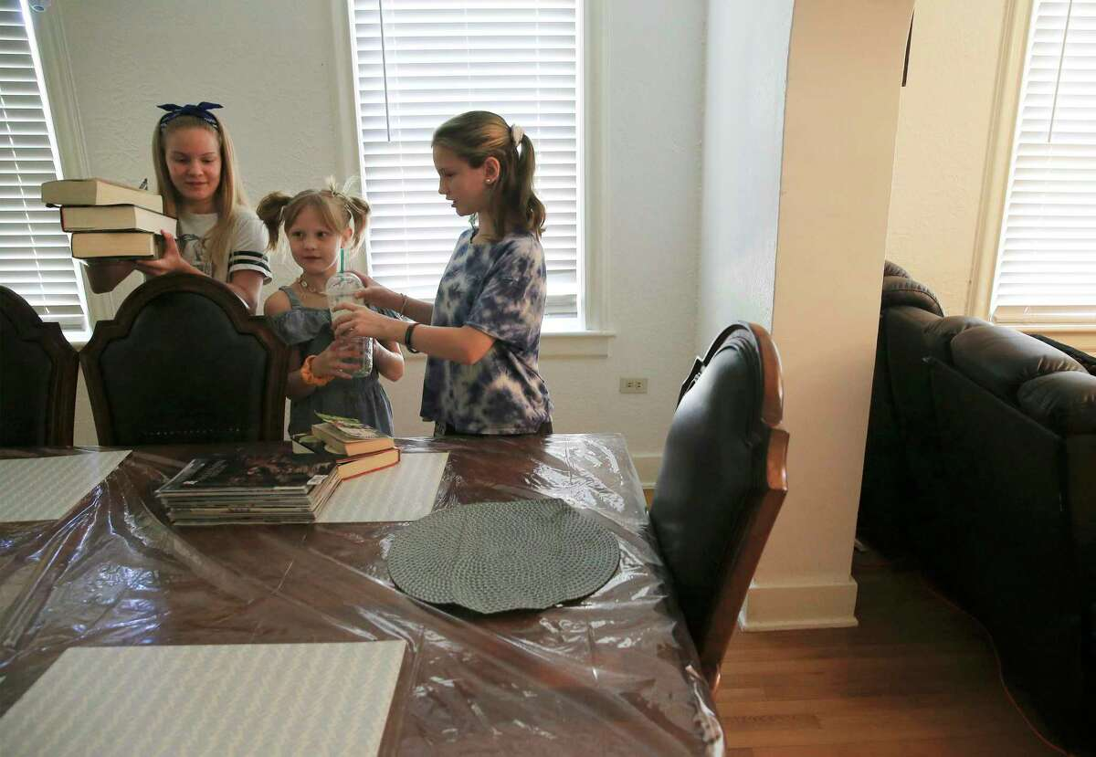 Tiffany Richards' three daughters-from left, Avanell, Amelia and Avee-bring out books to read Thursday at the dining table.