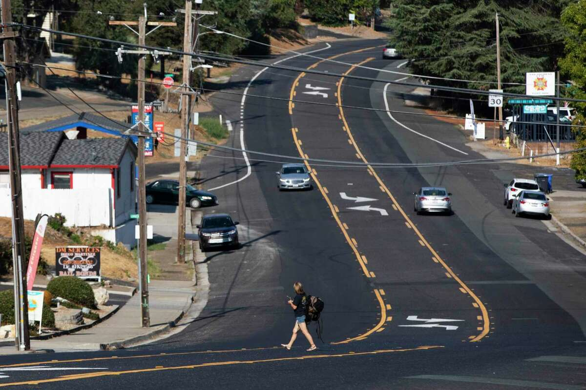 A woman crosses the main road into in San Andreas in Calaveras County, where voters signed the petition to remove Newsom at a higher rate than anywhere else in California.