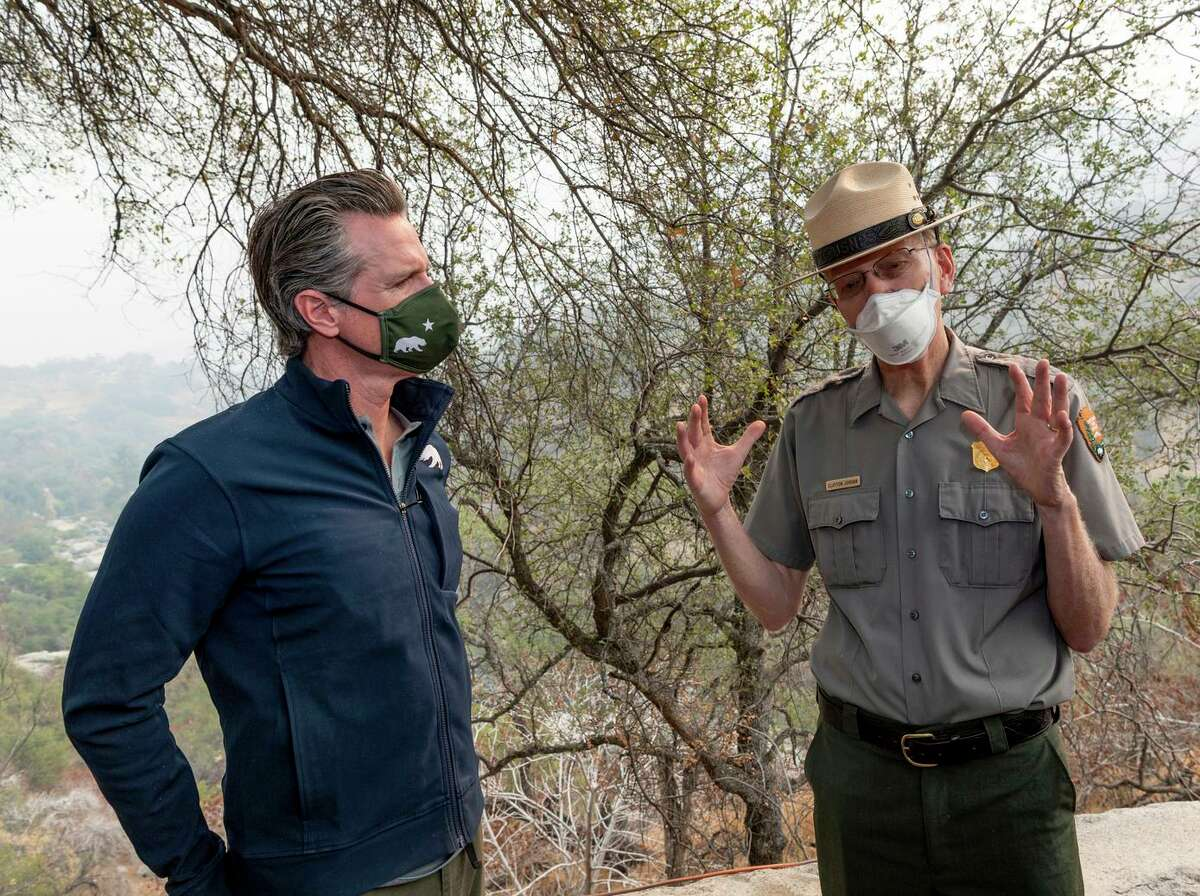 Gov. Gavin Newsom and Clay Jordan, superintendent of Sequoia and Kings Canyon National Park, talk Thursday after the California leader signed a $15 billion climate package into law.