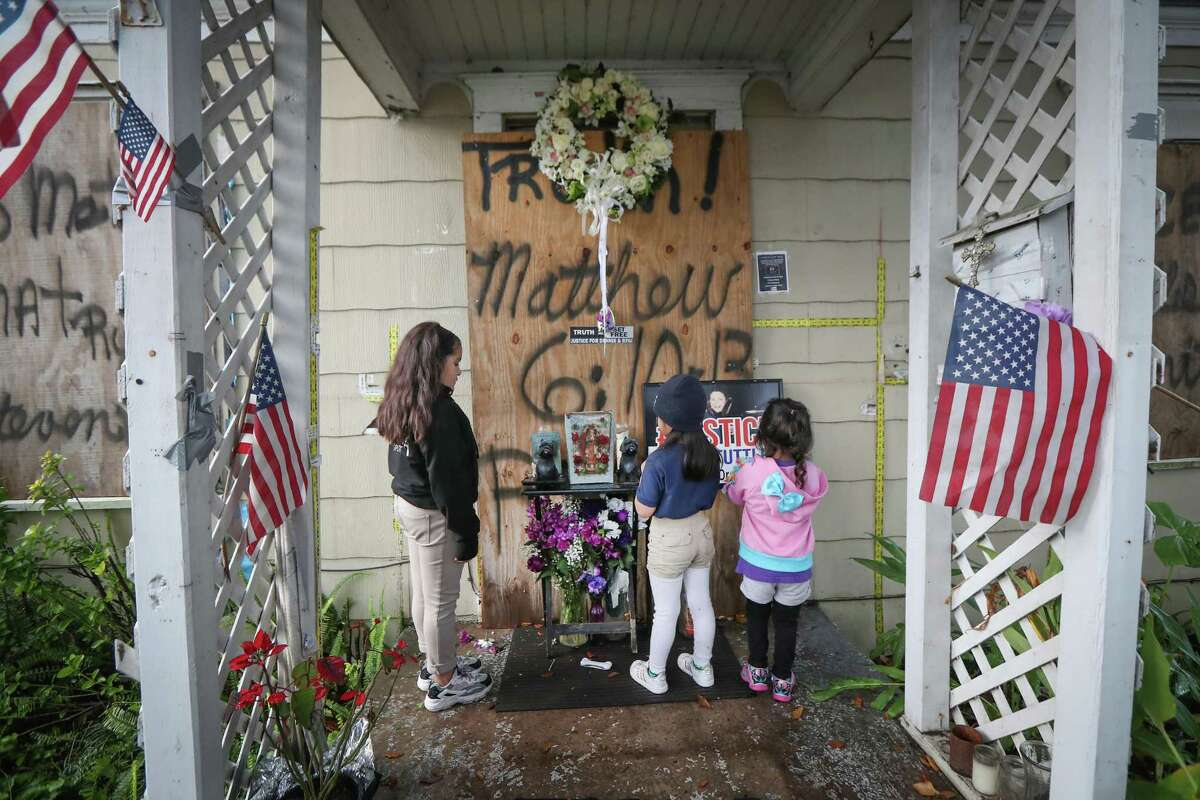 Katelynn, Melody and Emma Becerra pray for shooting victims Rhogena Nicholas and her husband, Dennis Tuttle, after a vigil at 7815 Harding St. on the anniversary of their deaths Tuesday, Jan. 28, 2020, in Houston.