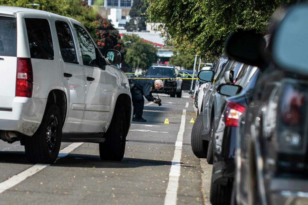 A member of the San Francisco Police Department photographs the scene of a homicide on Folsom Street between 16th and 17th Street in San Francisco, Calif. Friday, Sept. 24, 2021.