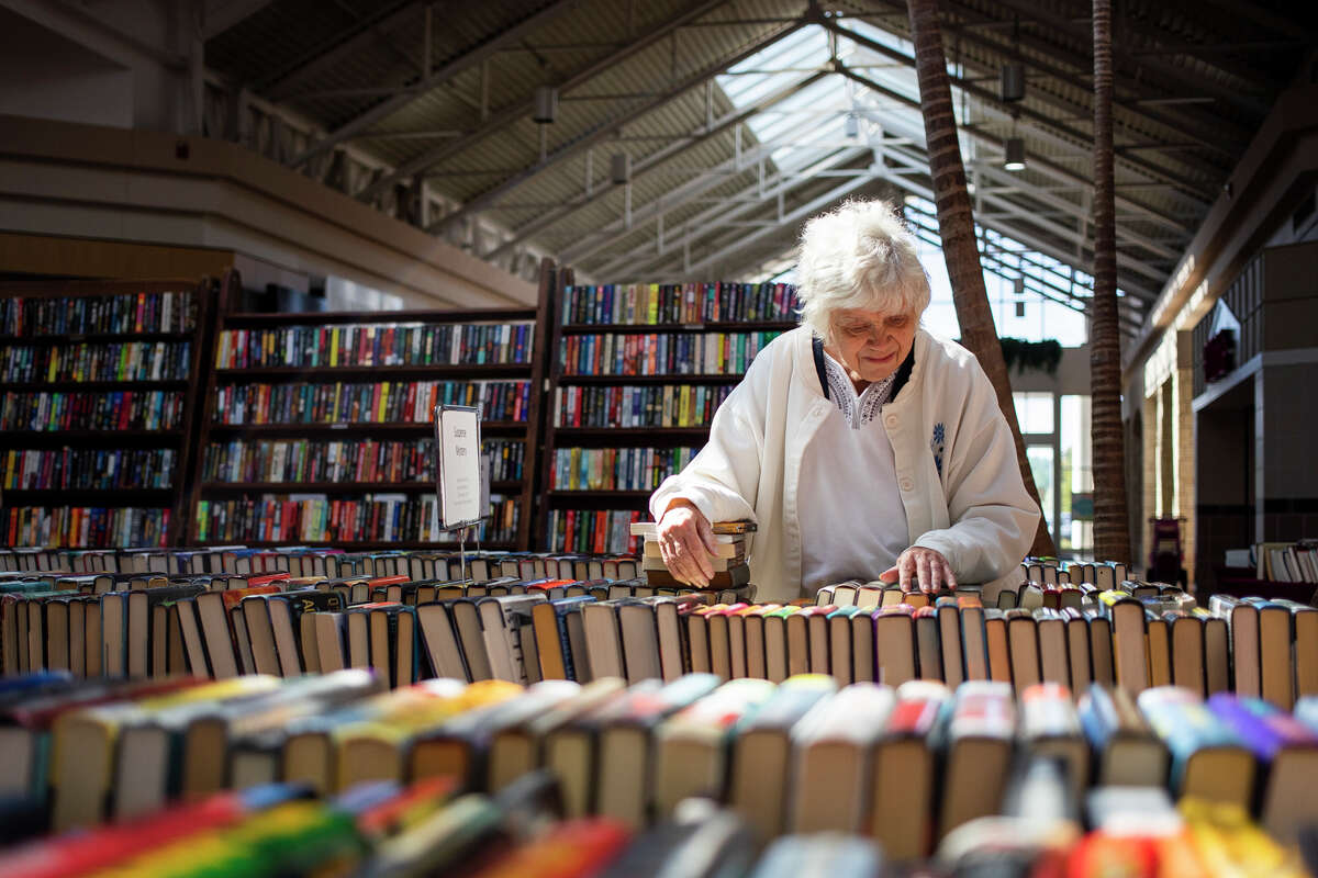 Susan Sadenwater of Freeland peruses used books during the American Association of University Women's (AAUW) Fall Used Book Sale Friday, Sept. 24, 2021 at the Midland Mall. (Katy Kildee/kkildee@mdn.net)