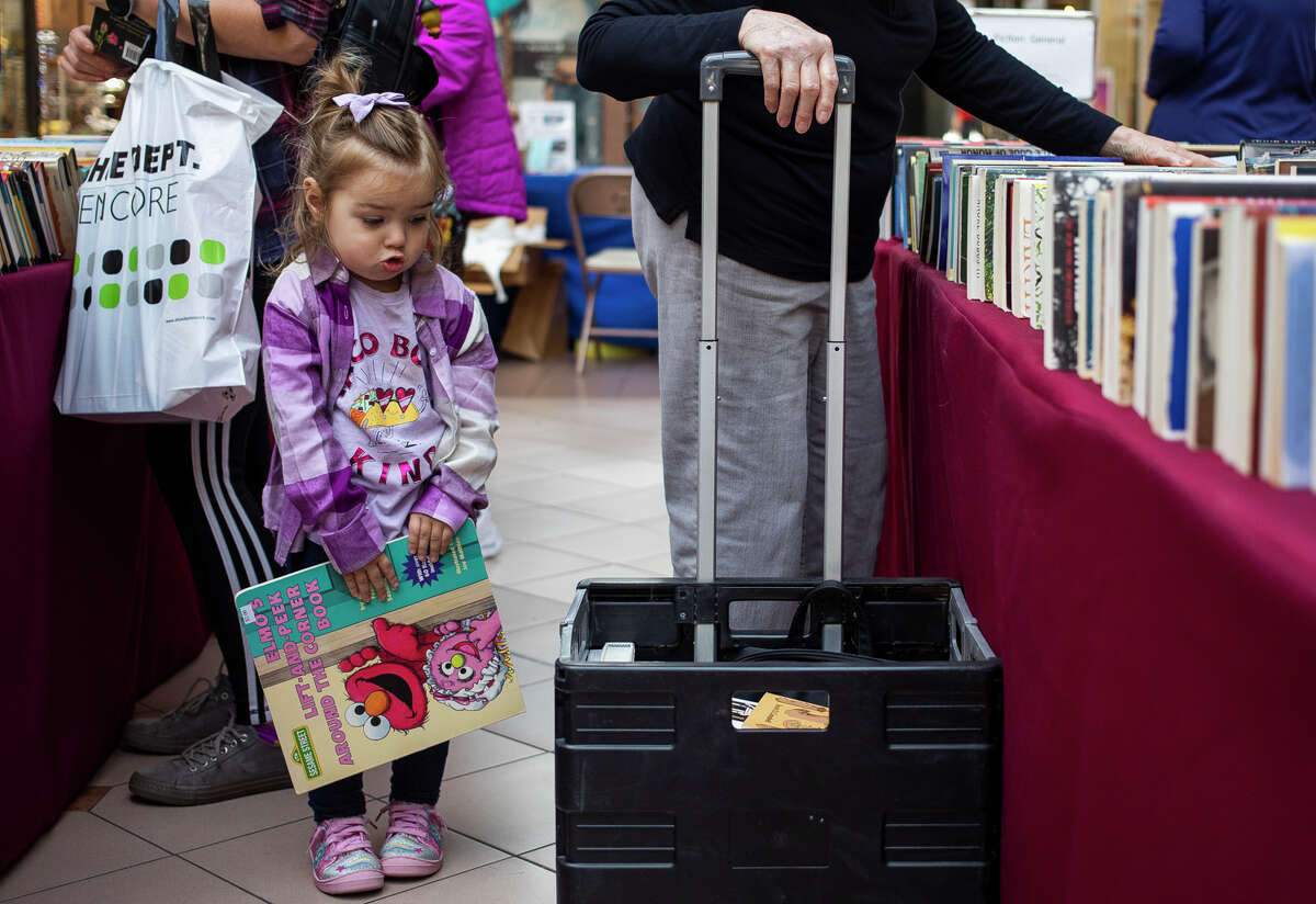 Kennedy Rechsteiner of Kawkawlin, 2, holds onto the book she picked out during the American Association of University Women's (AAUW) Fall Used Book Sale Friday, Sept. 24, 2021 at the Midland Mall. (Katy Kildee/kkildee@mdn.net)