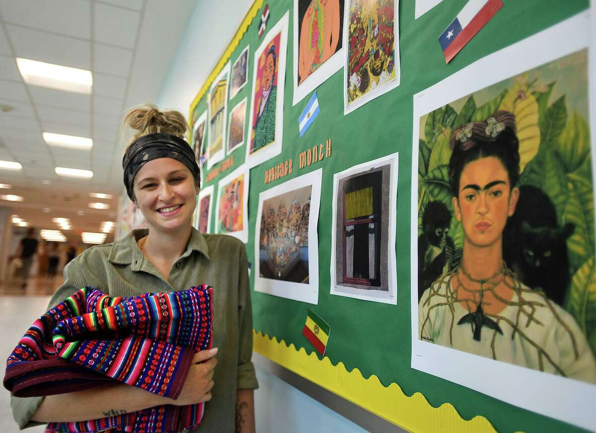 Staples High School biology teacher Kayla Iannetta with a bulletin board featuring Hispanic artists, one of many exhibits she has initiated for Hispanic Heritage Month at the school in Westport, Conn. on Thursday, September 23, 2021. Iannetta's father is Peruvian.