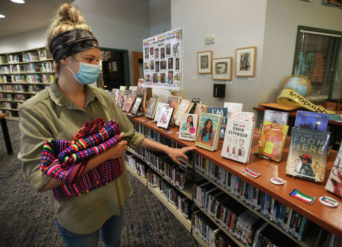 Biology teacher Kayla Iannetta shows the display of books by Hispanic authors in the Staples High School library, one of many exhibits for Hispanic Heritage Month at the school in Westport, Conn. on Thursday, September 23, 2021.