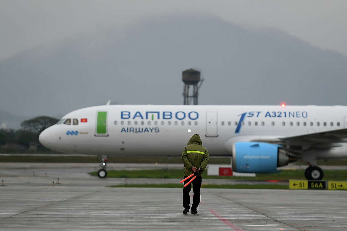 A Vietnamese groundstaff watches an Airbus A321Neo airplane of Vietnam's newly launched Bamboo Airways taxis on the runway during a welcoming ceremony on the airline's first day of operation at the Noi Bai Domestic airport in Hanoi on January 16, 2019.