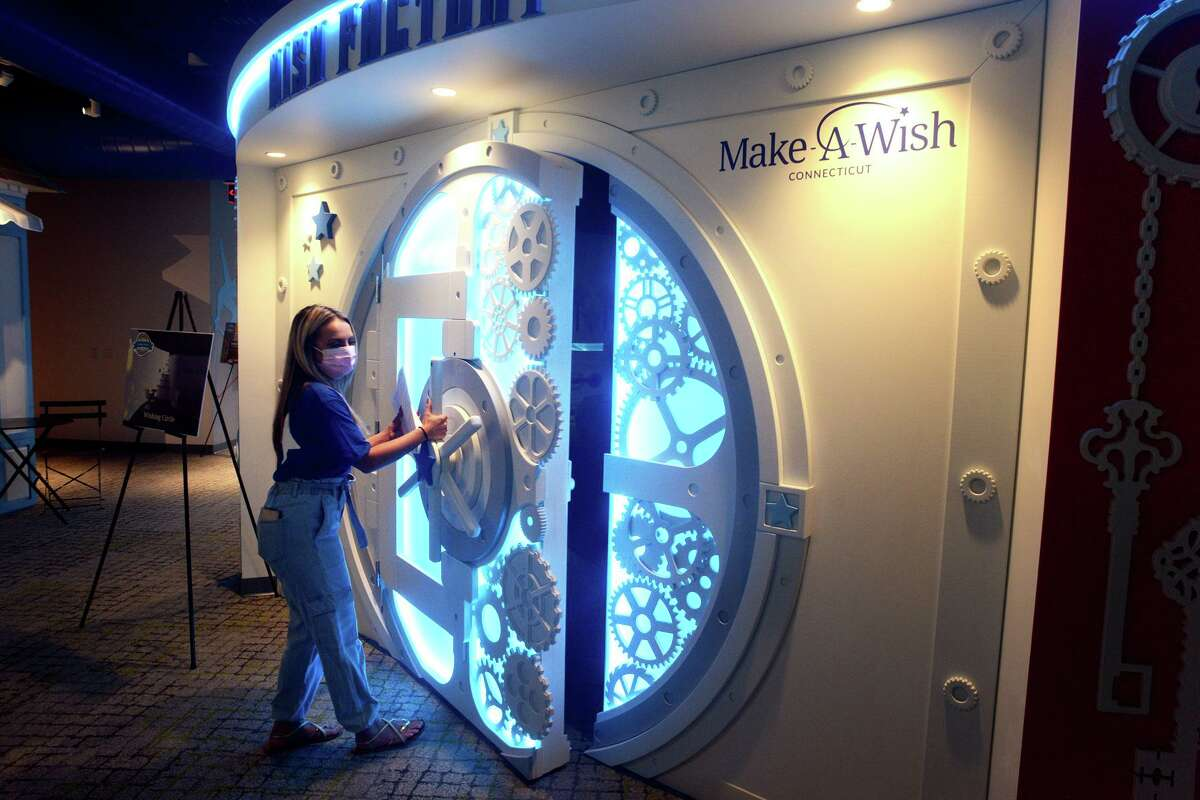 """Volunteer Jillian Duffy opens the door of the """"Wish Factory"""" last week at Make-A-Wish Connecticut's new headquarters in Trumbull."""