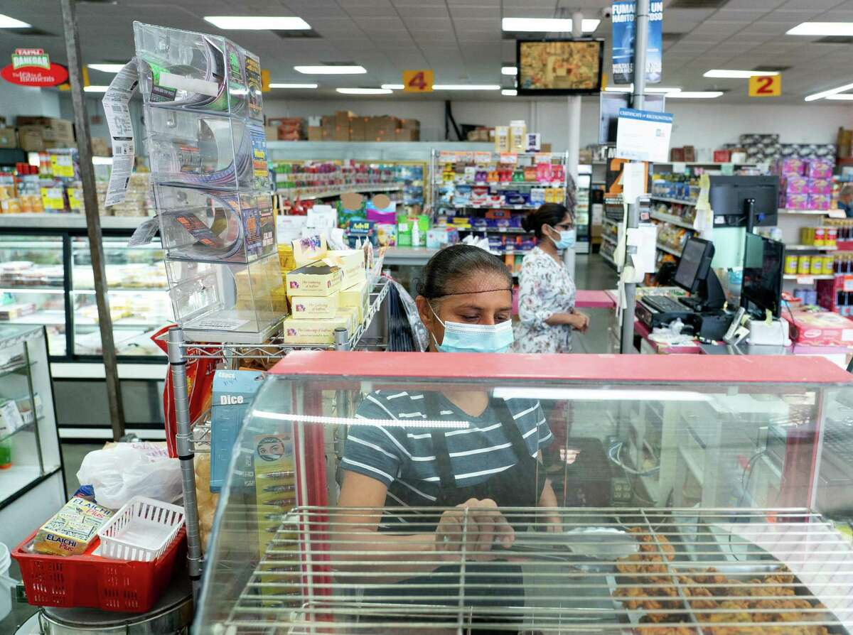 Asian Market cook Nafisa Momin, center, restocks fresh made samosas near the checkout line on Thursday, Sept. 23, 2021, in Sugar Land. The store caters to the Indian and Pakistani community in the area with specialties like basmati rice, spices, tea and other specialty foods. The Asian American population in the Houston-area suburbs is growing faster than any other segment of the population, according to data released last month by the U.S. Census Bureau.