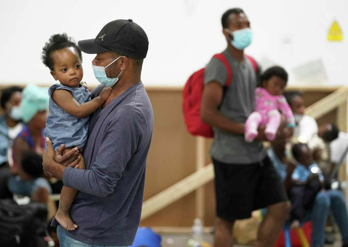 Abat Josma holds his year-old daughter, Walderlin, on Friday at a transitional center for Haitian migrants at the National Association of Christian Disaster Services in Houston.