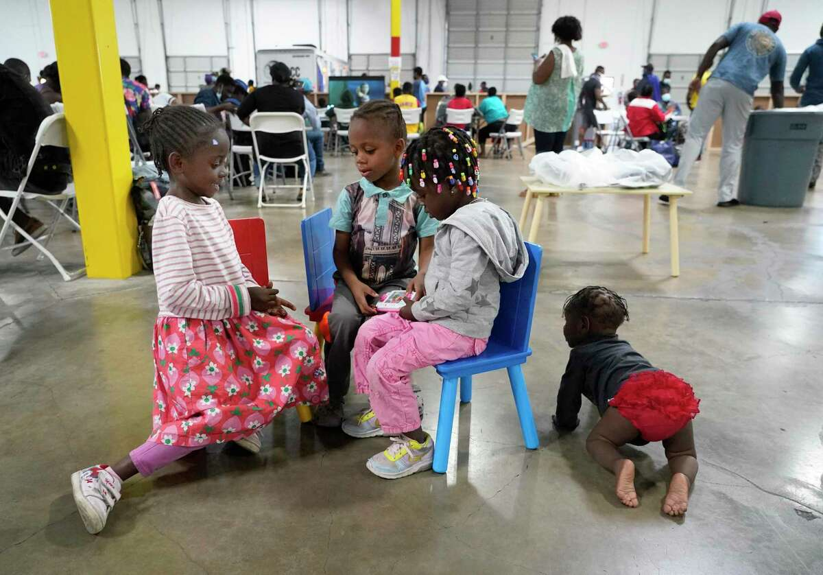 Children play at the transitional center for Haitian migrants in the National Association of Christian Disaster Services building Friday in Houston. A group of faith and civic leaders held a news conference in support of Haitian migrants.