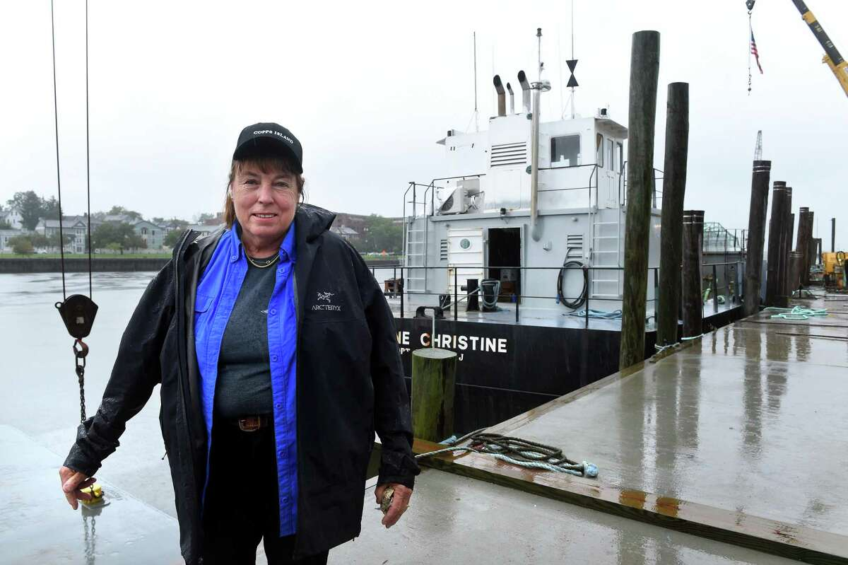 Copps Island Oysters farm stand manager Patty King is photographed by the oyster dredging boat, Jeanne Christine, on Quinnipiac Avenue in New Haven on September 24, 2021.