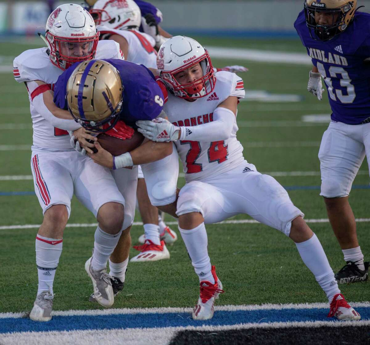 Midland High's Landry Walls (6) scores a touchdown as Odessa High's Zeke Garcia (24) and Mario Valdez attempt to tackle Friday, Sept. 24, 2021 at Grande Communications Stadium. Jacy Lewis/Reporter-Telegram