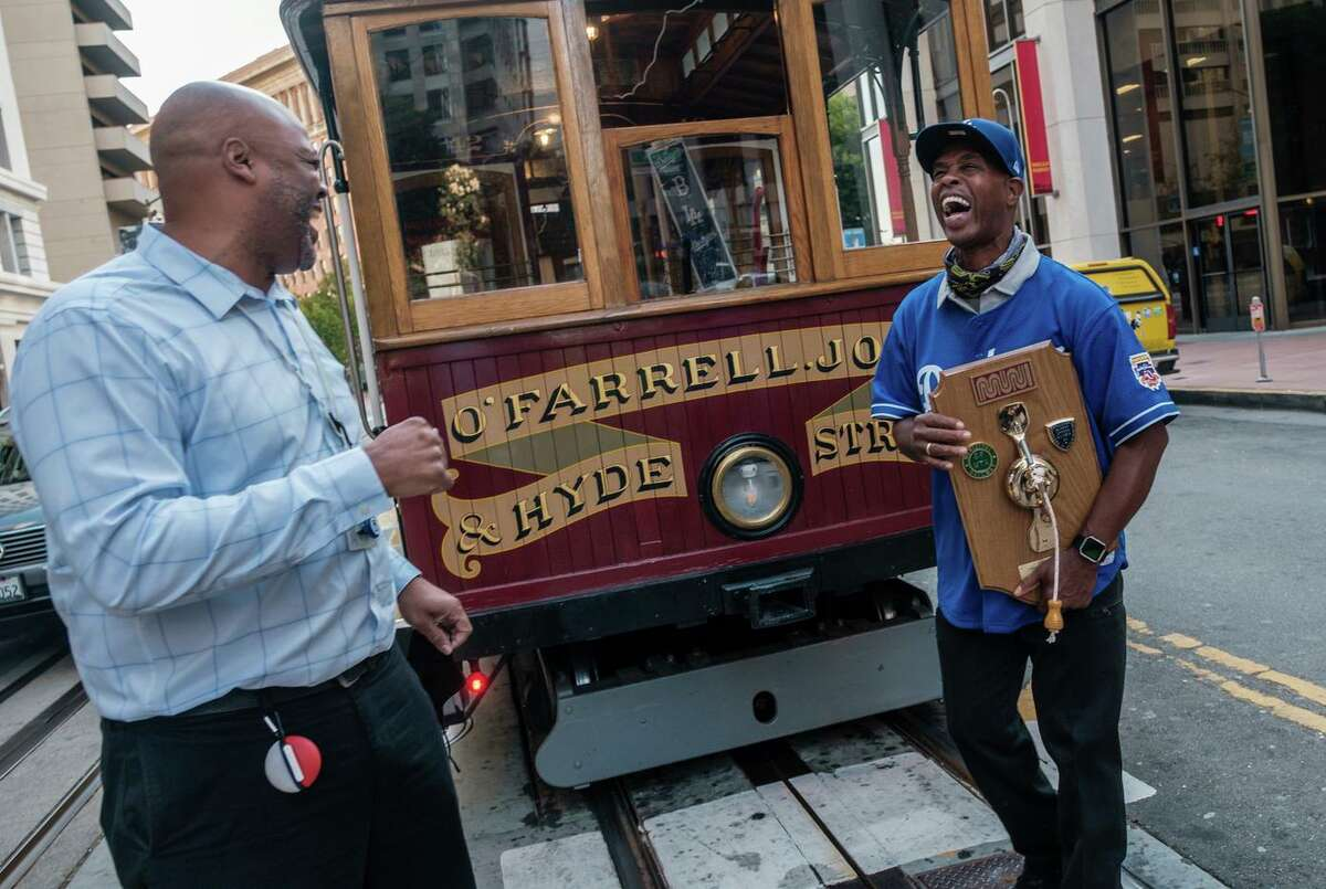 Cable car gripman Byron Cobb (right) jokes with a colleague on his last shift before retirement.