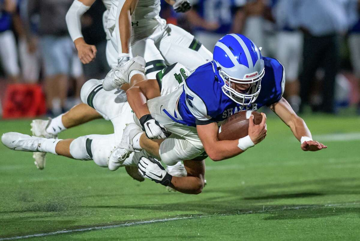 Shaker quarterback Jake Iacobaccio dives for yardage while in the grasp of Shenendehowa defender Anthony Caprara during a Class AA matchup at Shenendehowa High School in Clifton Park, NY, on Friday, Sept. 24, 2021. (Jim Franco/Special to the Times Union)