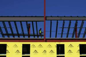 A crew continues construction on a new apartment building near St. Andrews Episcopal Church on Washington Boulevard in Stamford, Conn. Wednesday, Jan. 20, 2021.