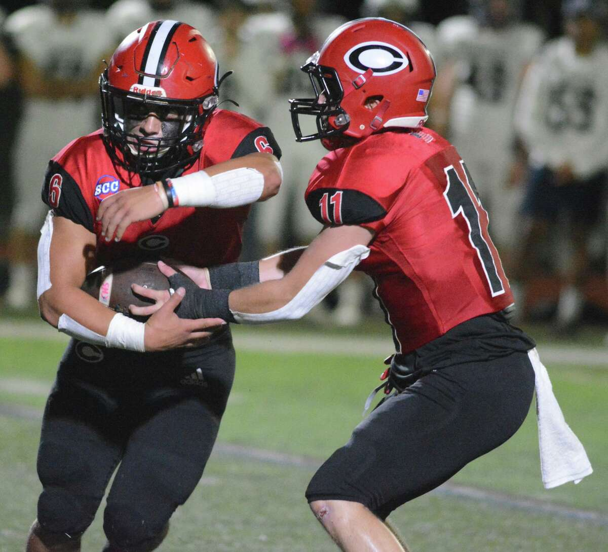 Christian Russo of Cheshire takes the handoff from quarterback Mike Simeone during a football game on Friday.