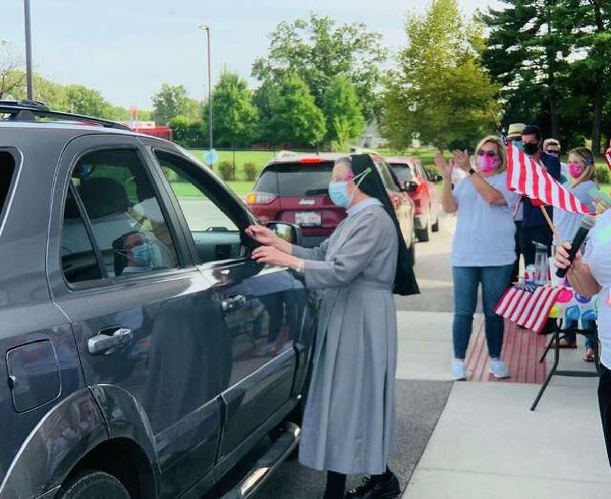 A cancer survivor is greeted Friday afternoon at a drive-by parade for cancer patients and survivors at OSF HealthCare Saint Anthony's Health Center in Alton. Additional photos can be seen at thetelegraph.com.