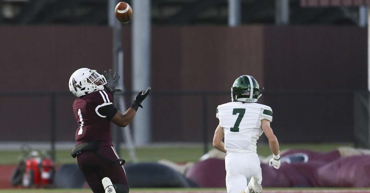 Pearland Oilers wide receiver Izeal Jones #1 catches a 63 yard touchdown reception against Strake Jesuit Fighting Crusader defensive back Gabe Hyzak #7 defends on the play in a District 23-6A high school football game on September 24, 2021 at The Rig in Pearland , TX.