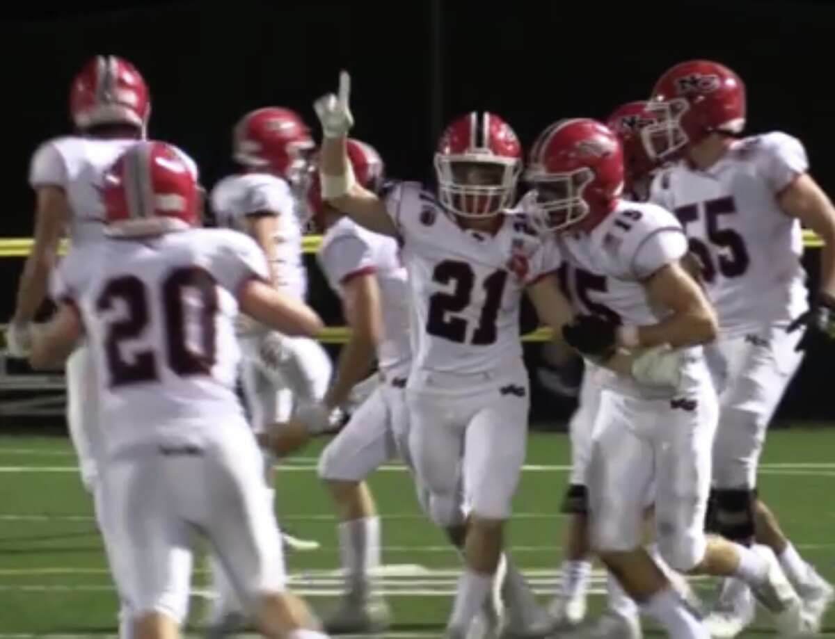 Dylan Murray (21) celebrates after sealing New Canaan's 28-18 victory over Hand with a 22-yard interception return touchdown Friday, Sept. 24, 2021 at Strong Field, Madison Surf Club.