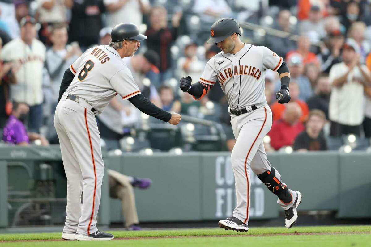DENVER, COLORADO - SEPTEMBER 24: Tommy La Stella #18 of the San Francisco Giants is congratulated by Ron Wotus #23 as he circles the bases after hitting a lead off home run against the Colorado Rockies in the first inning at Coors Field on September 24, 2021 in Denver, Colorado. (Photo by Matthew Stockman/Getty Images)