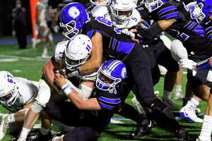 Darien's Jack Barber (92), at top, and teammate Sean Quick (31) bring down Newtown's Andrew Jacobs (11) during high school football action in Darien, Conn., on Friday September 18, 2021.