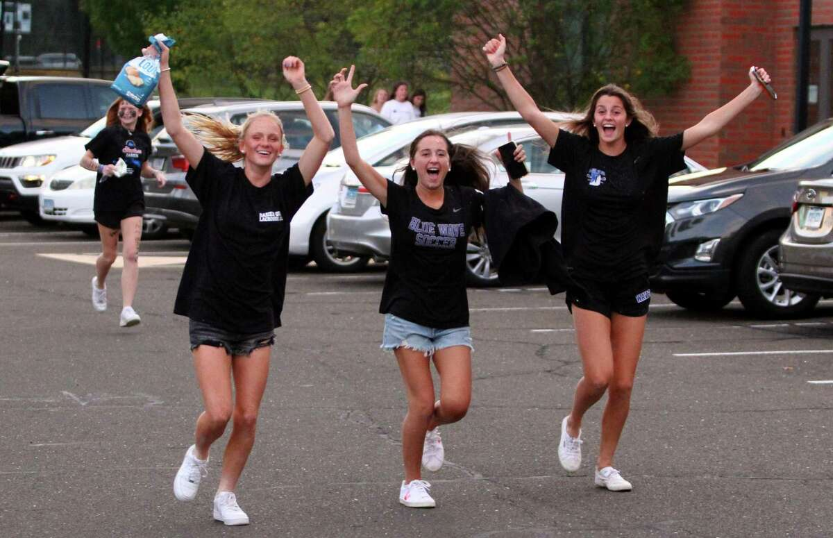 Darien high schoolers let out cheers as they rush to the stadium just before the start of football action between No. 1 Darien and No. 4 Newtown, in Darien, Conn., on Friday September 18, 2021.
