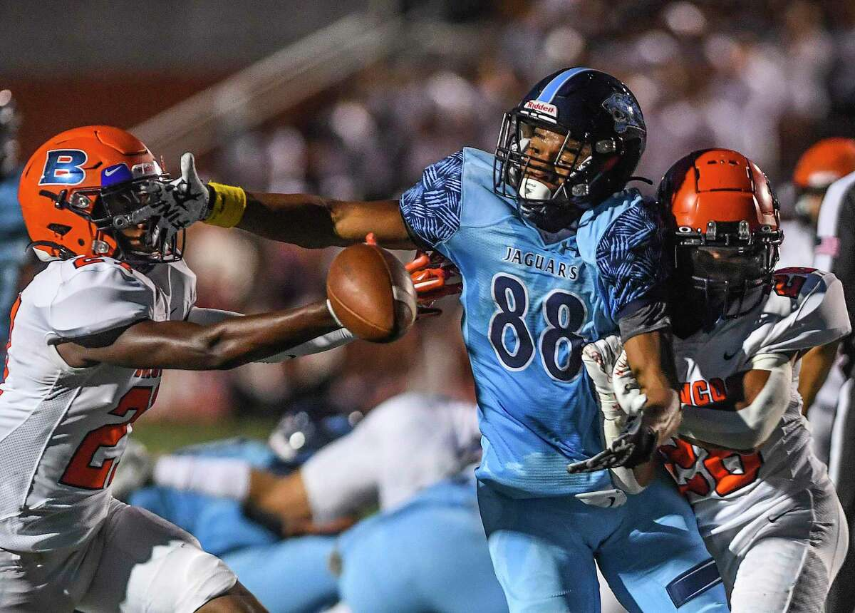 Johnson Jaguars receiver Canaan Fairley (88) has a passed ball knocked away by Brandeis defenders Tyson Short, left, and CJ King, right, during high school football action at Heroes Stadium on Friday, Sept. 24, 2021.
