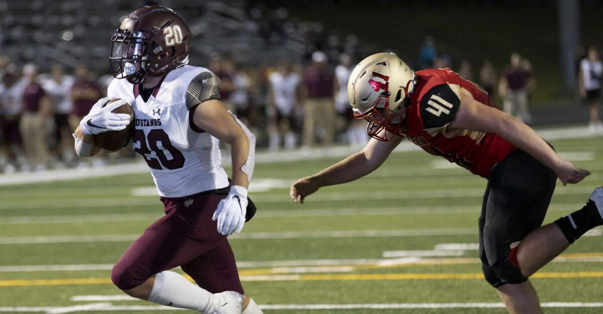 Magnolia West half-back Hunter Bilbo (20) scores a touchdown despite pressure from Caney Creek linebacker Clayton Redd (41) during the third quarter of a District 8-5A (Div. I) football game at Buddy Moorhead Stadium, Friday, Sept. 24, 2021, in Conroe.