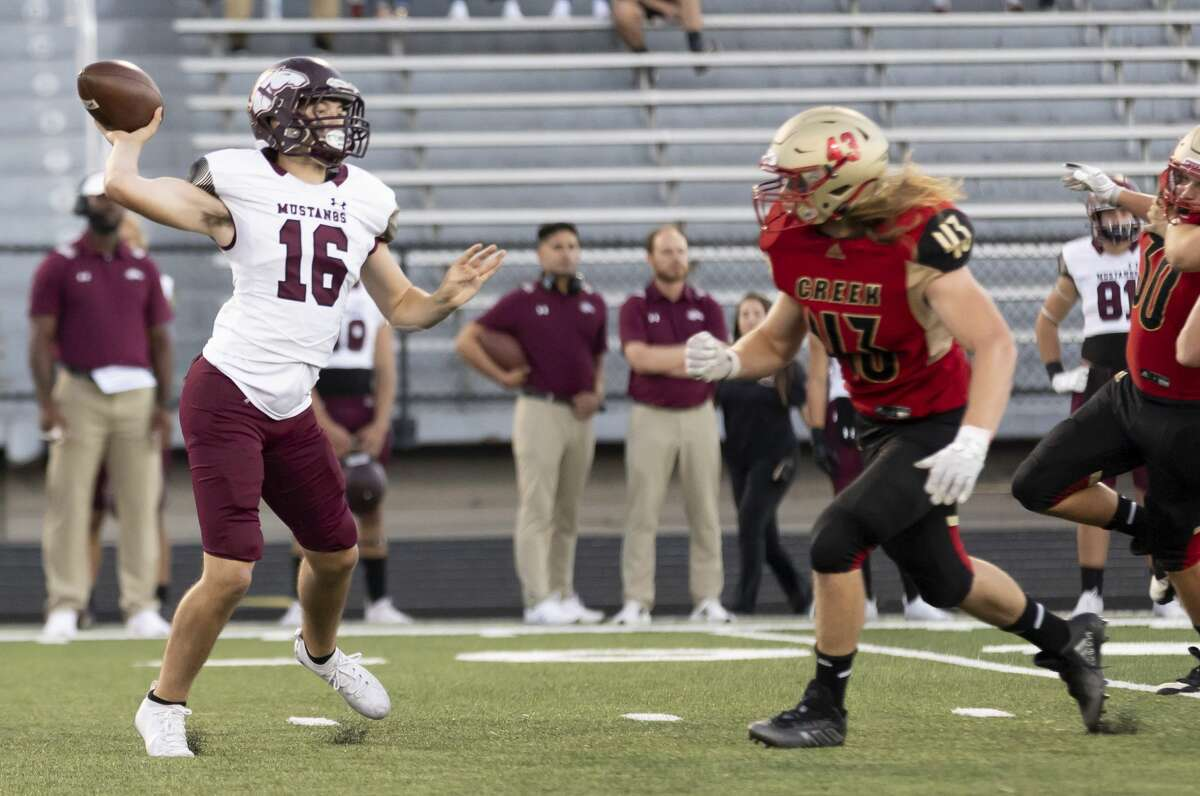 Magnolia West quarterback Ryan Ojeda (16) throws before Caney Creek defensive lineman Tristen Brown (43) tackles him during the first quarter of a District 8-5A (Div. I) football game at Buddy Moorhead Stadium, Friday, Sept. 24, 2021, in Conroe.
