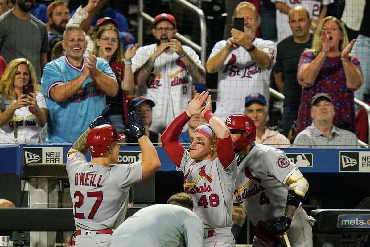 Fans watch St. Louis Cardinals' Tyler O'Neill (27) celebrates with Harrison Bader (48) and Yadier Molina (4) after O'Neill hit a two-run home run during the eighth inning of the team's baseball game against the New York Mets on Tuesday, Sept. 14, 2021, in New York. (AP Photo/Frank Franklin II)