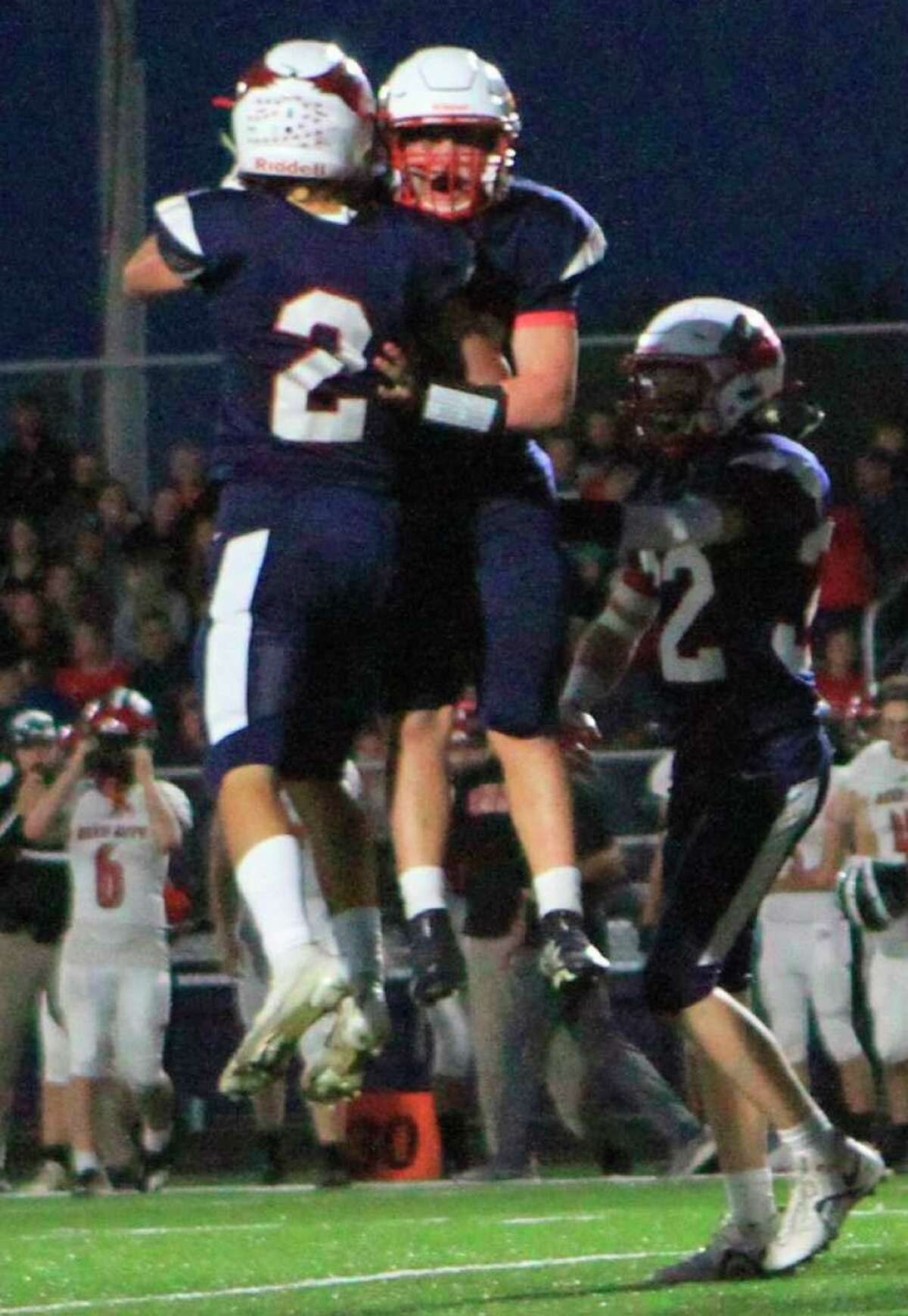 Big Rapids players, including Bradyn Foster (2), celebrate a play against Reed City on Friday. (Pioneer photo/Joe Judd)