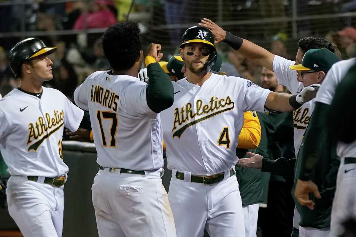Oakland Athletics' Chad Pinder (4) is congratulated by teammates after hitting a grand slam home run against the Houston Astros during the seventh inning of a baseball game in Oakland, Calif., Friday, Sept. 24, 2021. (AP Photo/Jeff Chiu)