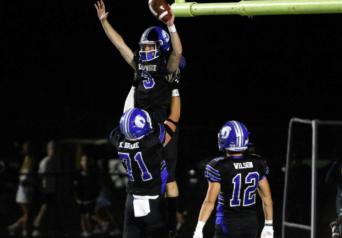 Darien's Miles Drake leaps into the arms of teammate Karson Drake after scoring a touchdown against Newtown on Friday night.