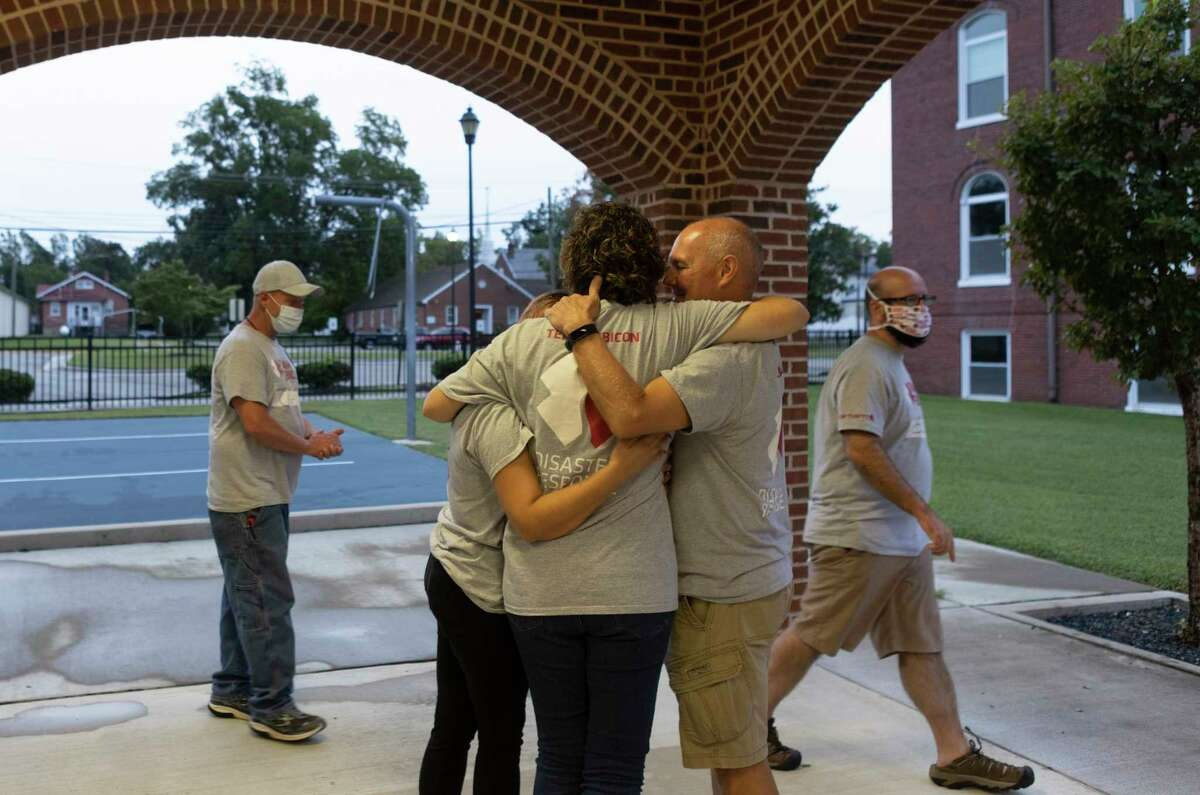 Members of Team Rubicon, a volunteer disaster-relief organization, hug after a daily debriefing meeting on Sept. 16 in Blackstone, Va.