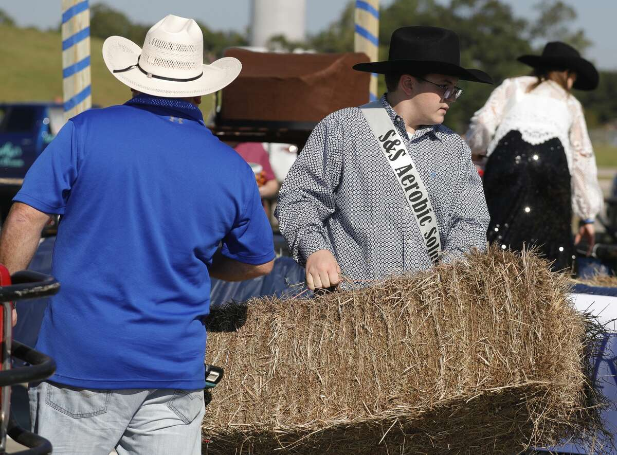Lance Sessum carries a bail of hay to a float before the annual East Montgomery County Fair and Rodeo parade, Saturday, Sept. 25, 2021, in New Caney.