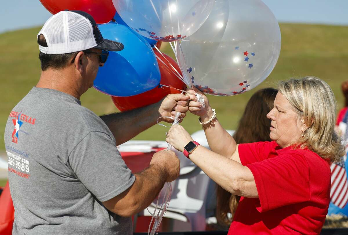 Holly Juneau, with the East Montgomery County Republican Women?•s - PAC, helps Randal Moore with balloons before the annual East Montgomery County Fair and Rodeo parade, Saturday, Sept. 25, 2021, in New Caney.