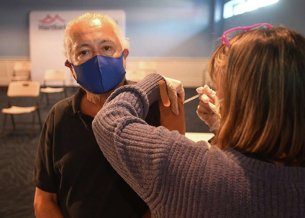 Rafael Merida, of Bridgeport, is first in line to receive the J&J Covid-19 vaccine from nurse Janet Cordova, RN, at a free vaccination clinic at the Hartford Healthcare Amphitheater in Bridgeport, Conn. on Wednesday, August 25, 2021.